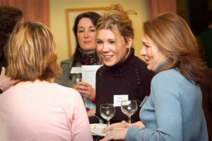 Image of networking - two women clutching documents and talking